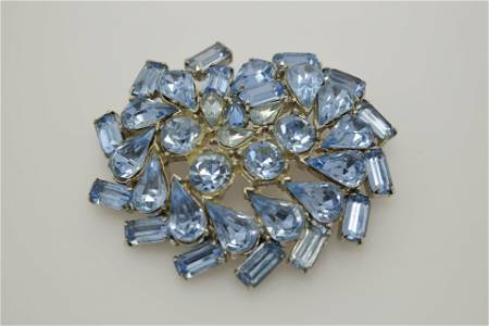 A vintage pin/brooch with light blue stones.