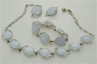 A vintage necklace, bracelet, and earring set of grey