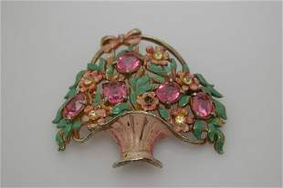 A vintage enamel pin/brooch with pink and clear stones.