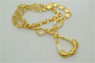A gold tone and white plastic necklace.