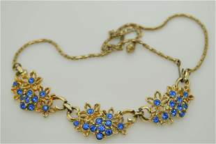 A vintage gold tone necklace with blue rhinestones.