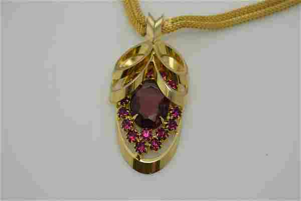 A vintage gold tone necklace with multi shades of pink