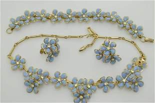 A vintage necklace, bracelet, and earring set of light