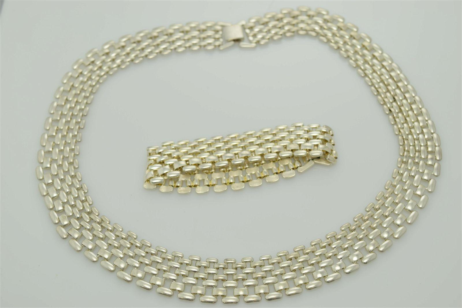 A silver tone necklace and bracelet set.