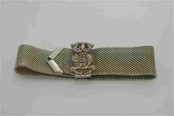 A silver tone mesh bracelet with an owl on clasp.