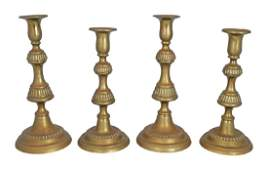 SET OF FOUR GEORGIAN BRASS CANDLESTICKS