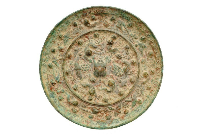 A Chinese bronze 'lion and grapevine' circular mirror,