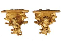 PAIR OF CARVED GILT WOOD CHERUB SUPPORTED WALL BRACKETS