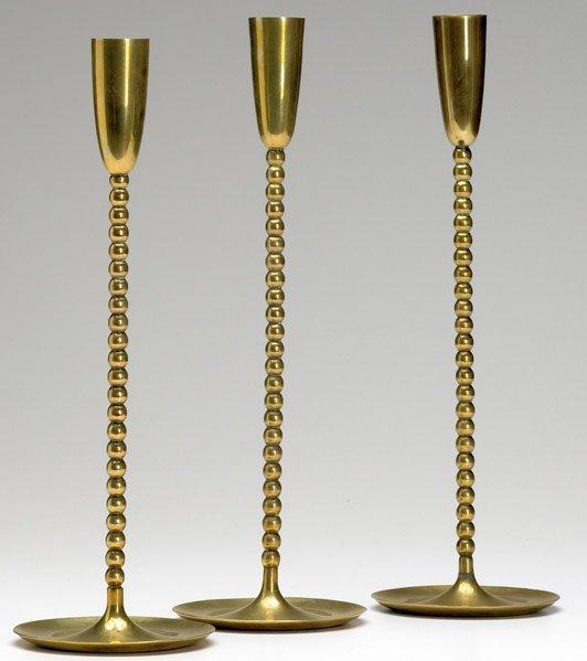 620: FRANZ HAGENAUER Set of three brass candlesticks.