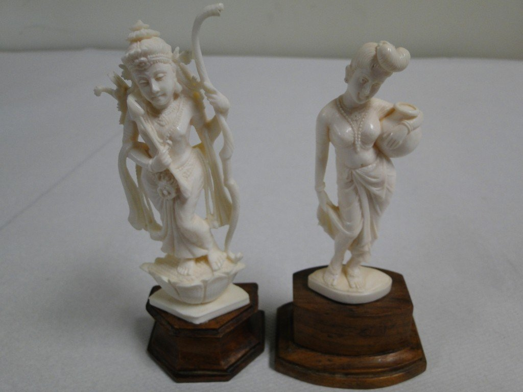 24: Two carved South East Asian ivory figures on stands