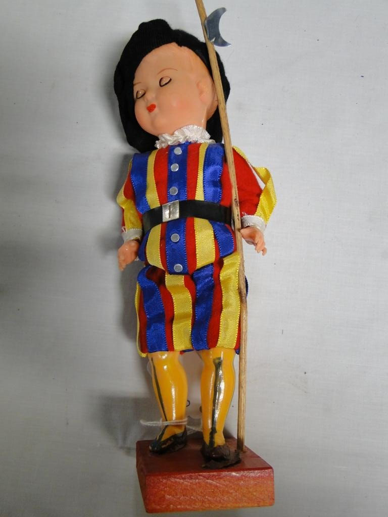 14: Celluloid Italian guard doll on wooden base with sl