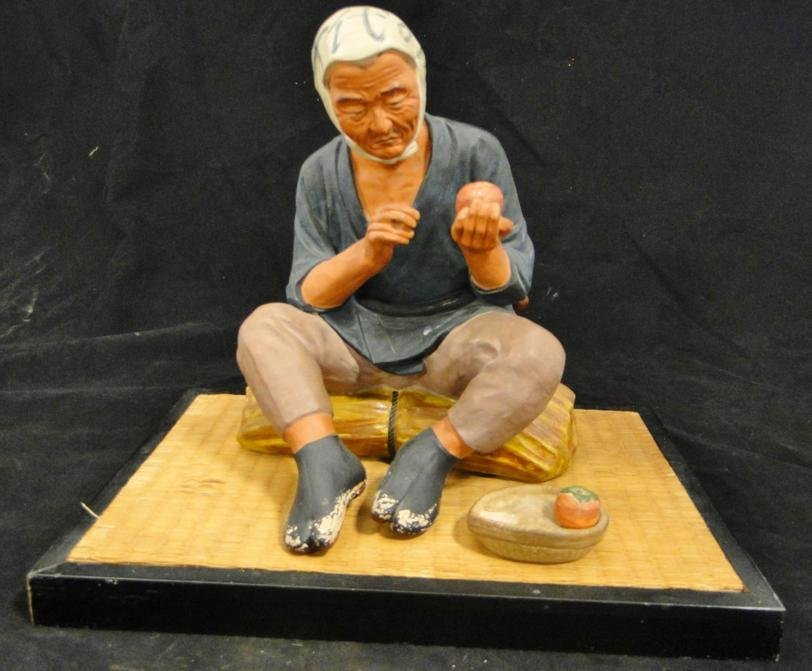 A large terracotta Japanese figure of a man with a