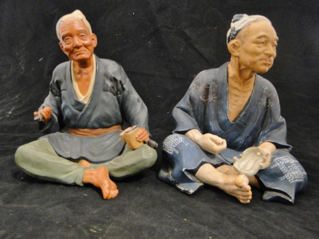 Two hand painted Japanese terracotta figures seated,
