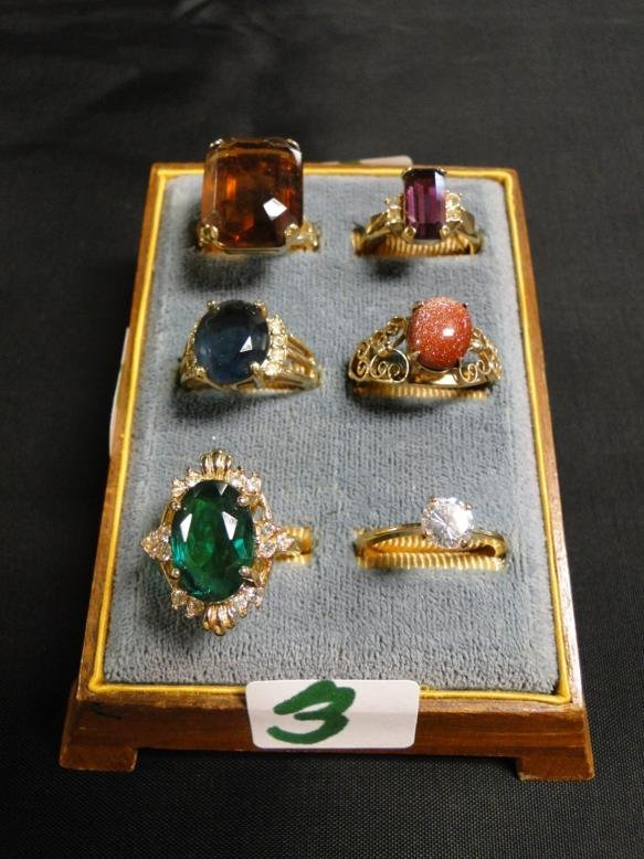 6 rings with colored stones in a 1920's ring holder.