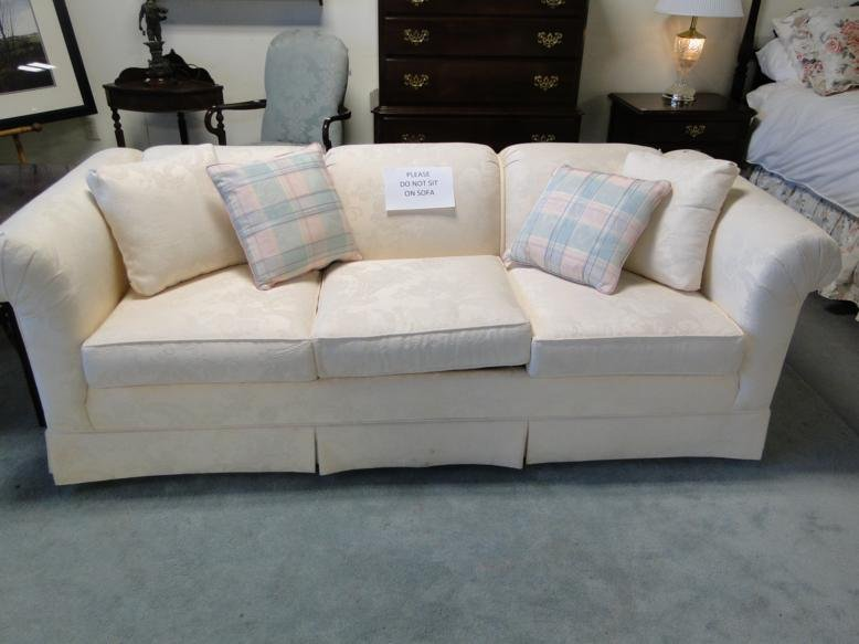 A white brocade, three-cushion sofa in excellent