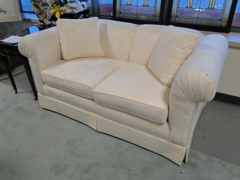 A white brocade, two-cushion sofa in excellent