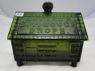 A green pressed glass advertising covered container in