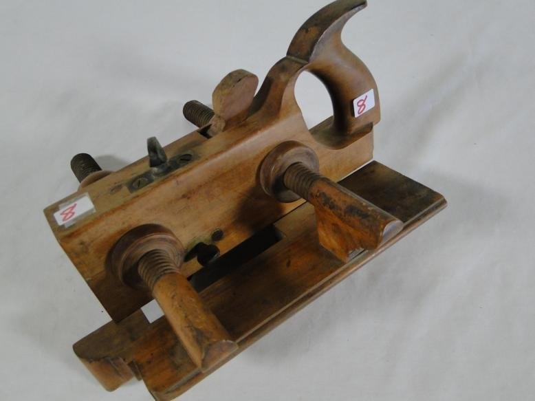 An antique wooden adjustable molding plane with handle