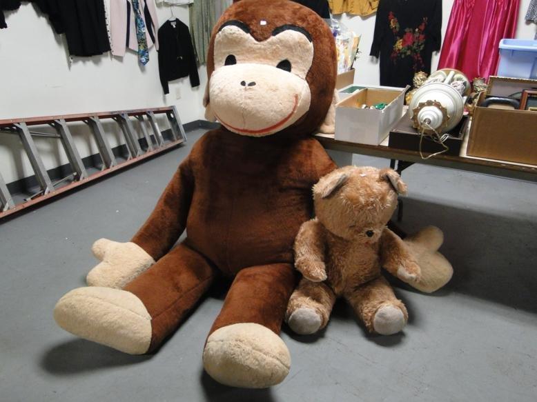 Large Curious George along with stuffed teddy bear