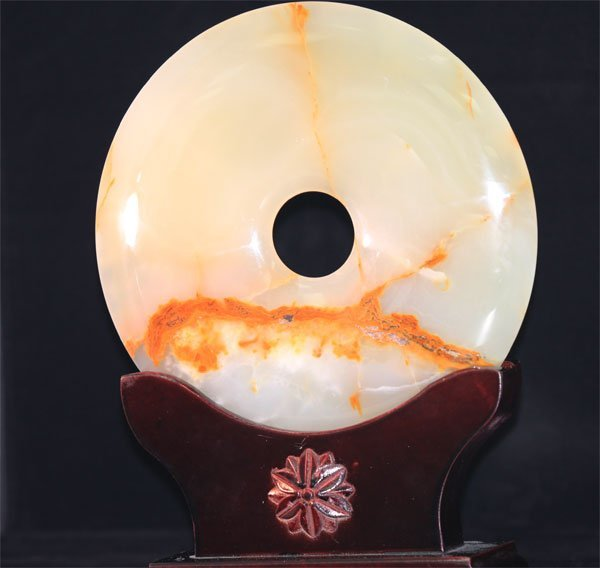 ROUND JADE STATUE WITH ANTIQUE WOOD BASE.