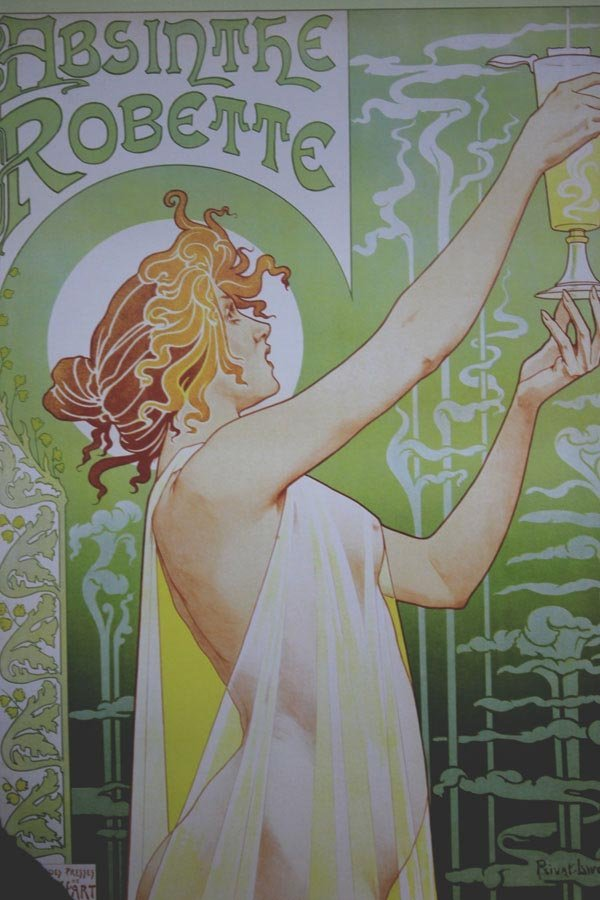 Woman holding up a glass of absinthe