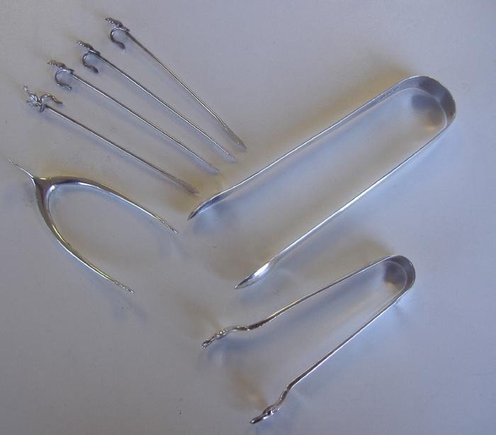 22: 3 Pair of Sterling Sugar Tongs, 4 Cocktail Skewers