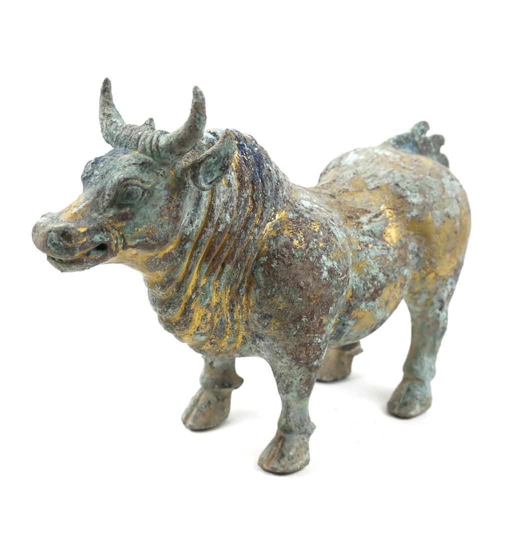 AN ASIAN GILT-BRONZE FIGURE OF A BULL