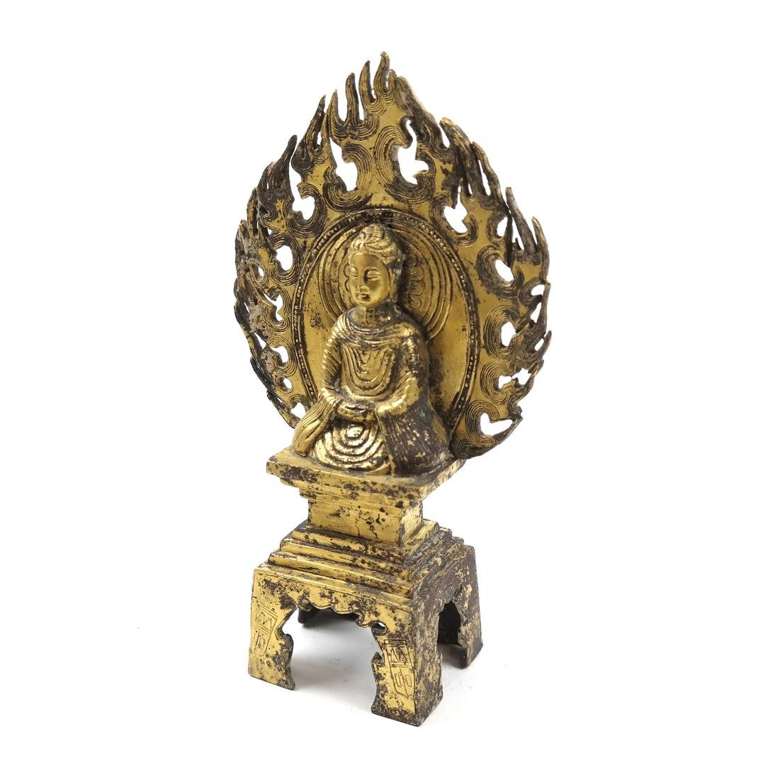 AN ASIAN SMALL GILT-BRONZE SEATED VOTIVE FIGURE OF