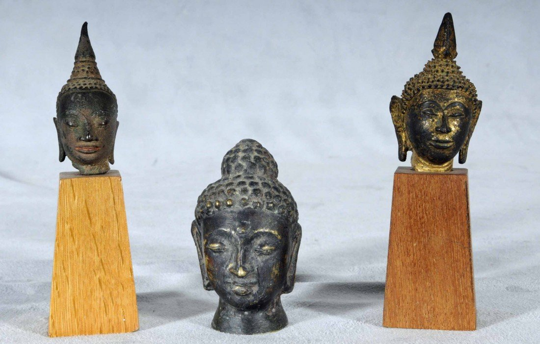 602: 3 ASIAN BRONZE BUDDHA HEADS. TWO ARE ON ON WOODEN