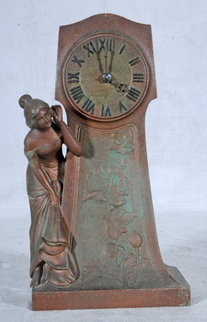 8: ART DECO SPELTER CLOCK W/ A LADY LISTENING TO THE CL