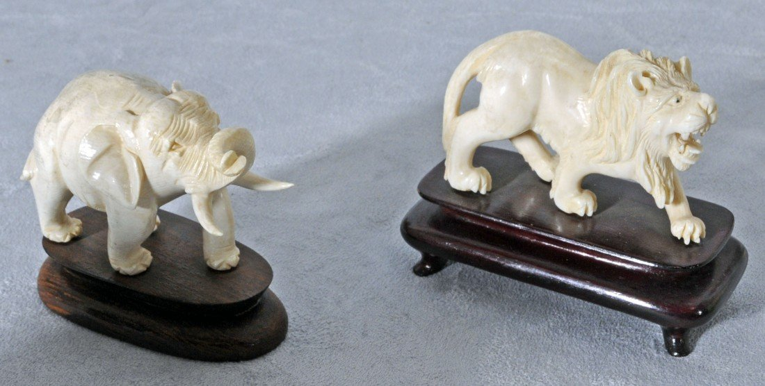 24: TWO ORIENTAL CARVED IVORY ANIMALS. A LION AND AN EL