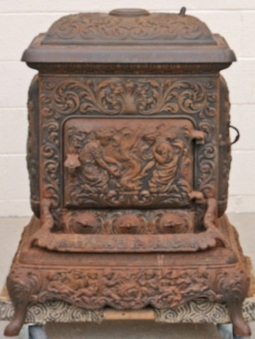 104: ANTIQUE CAST IRON POT BELLY STOVE. FIGURAL DECORAT