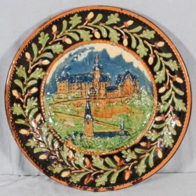 GERMAN MAJOLICA PLATE.  DECORATED W/ A CASTLE IN RE