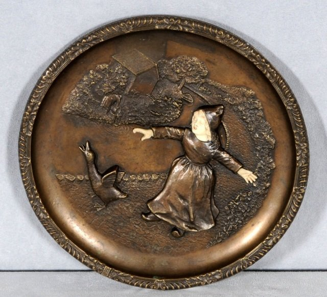 1: ROUND BROWN METAL PLATE DECORATED W/ A FIGURE OF A C