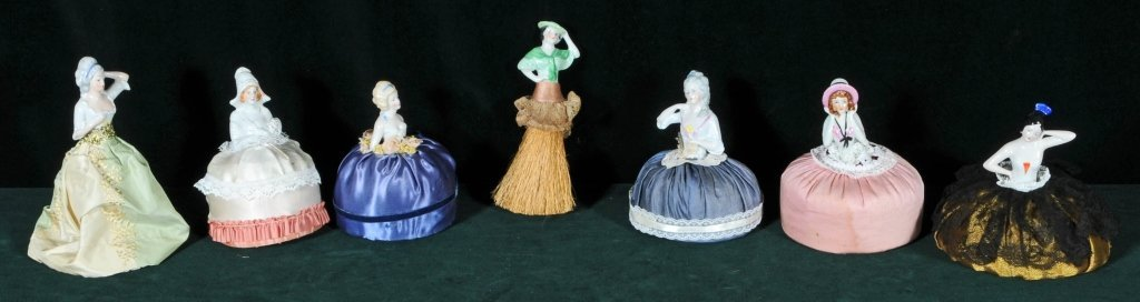 7 PORCELAIN PIECES. CONSISTING OF 6 PIN CUSHIONS, AND A