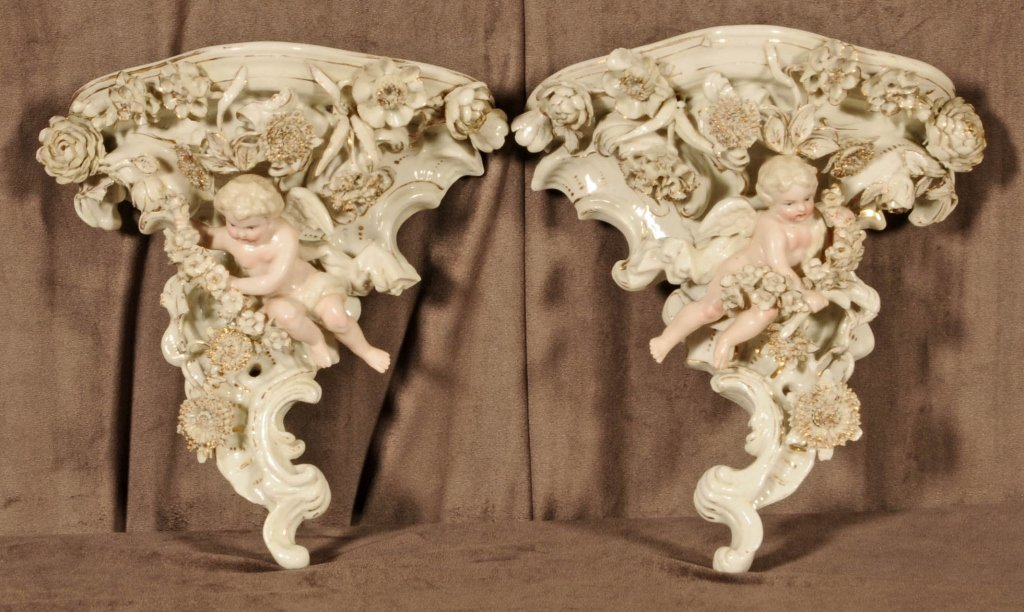 PAIR OF PORCELAIN WALL BRACKETS. GILT FLOWERS AND CUPID