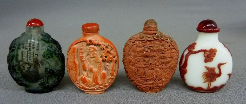 4 carved snuff bottles. One is Cinnabar with a relief s