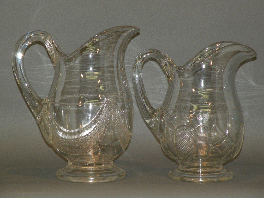 103: 2 colorless pattern glass pitchers