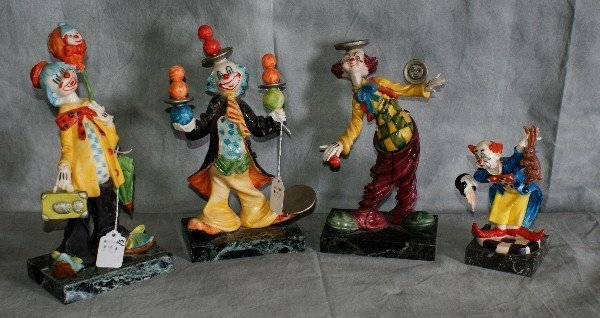 15: Four clowns on marble bases.