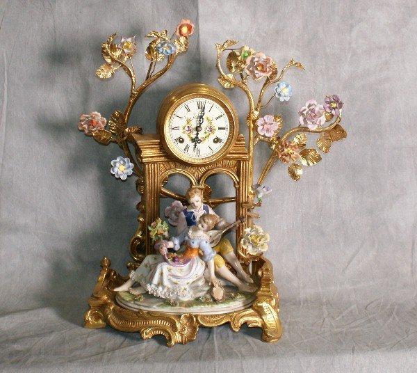 "Bronze and porcelain figural clock. H:16.5"" L:15.5"""