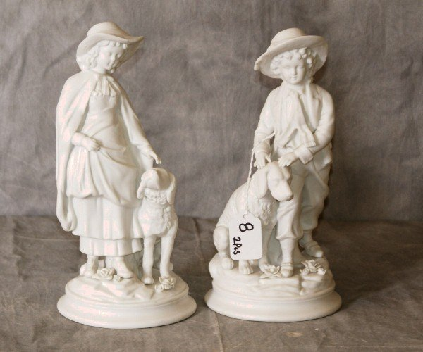 Pair of parian porcelain figures of children with dogs.