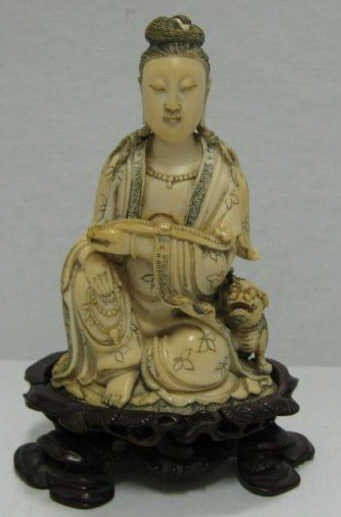 667: CHINESE IVORY SEATED GUAN YIN WITH FOO DOG