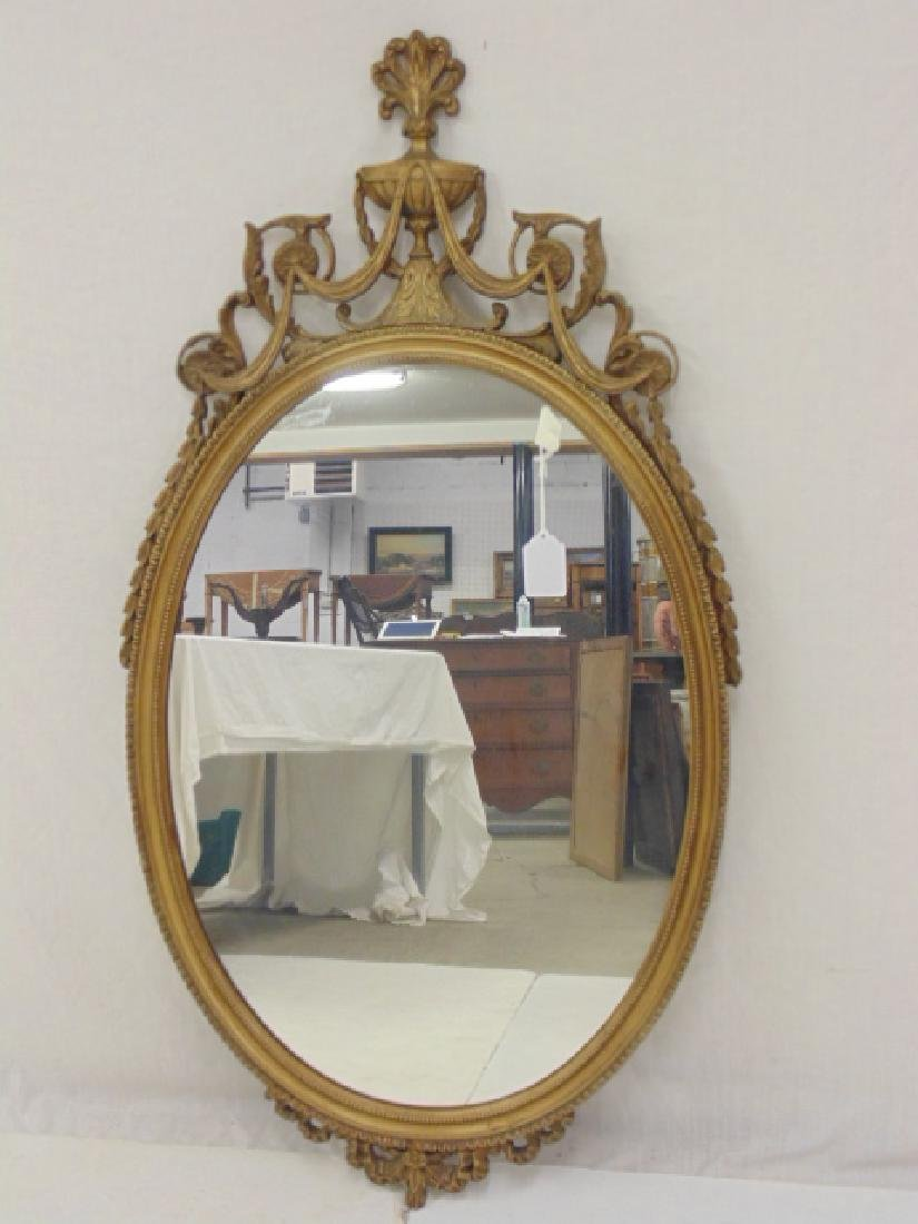 Oval gilt framed mirror, ribbon top