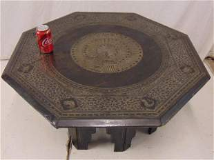 Octagonal table with carved peacock top sits on loose