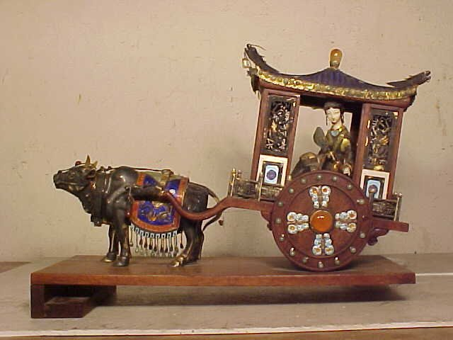 Silver enamel ox drawn carriage with figure inside