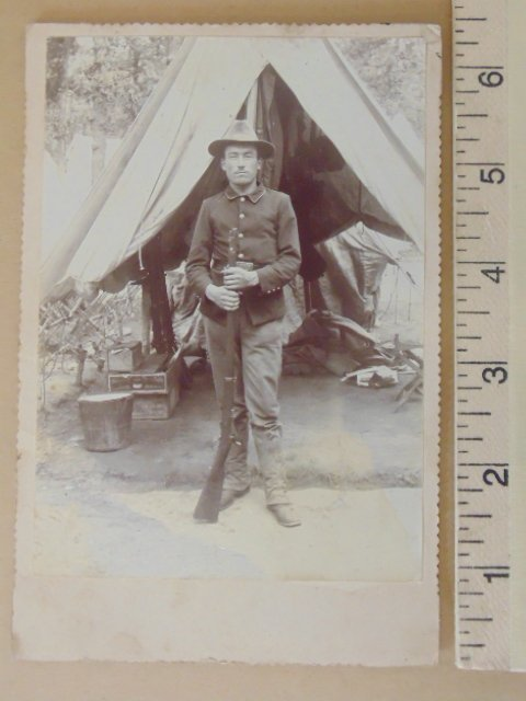 Photograph, soldier with rifle in front of tent