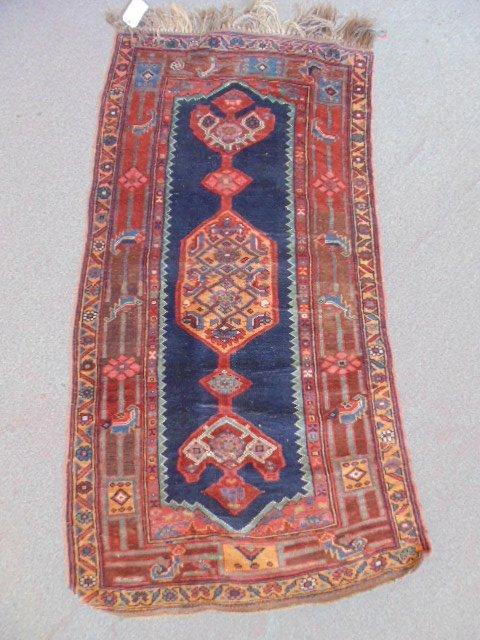 "Carpet, blue center, red border, 74"" by 39""."