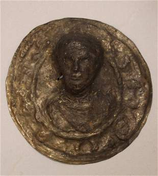A round Roman silver and metal plaque with head of a