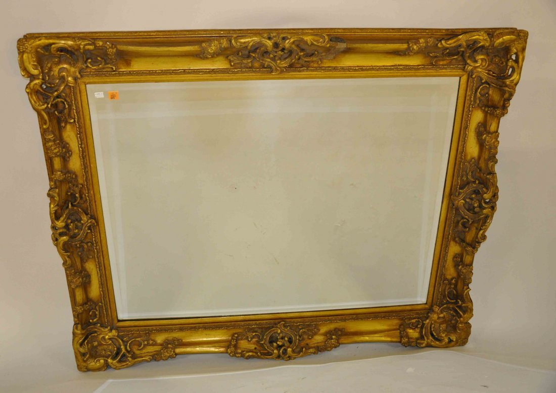 645: A large moulded gilt wall mirror, modern with beve