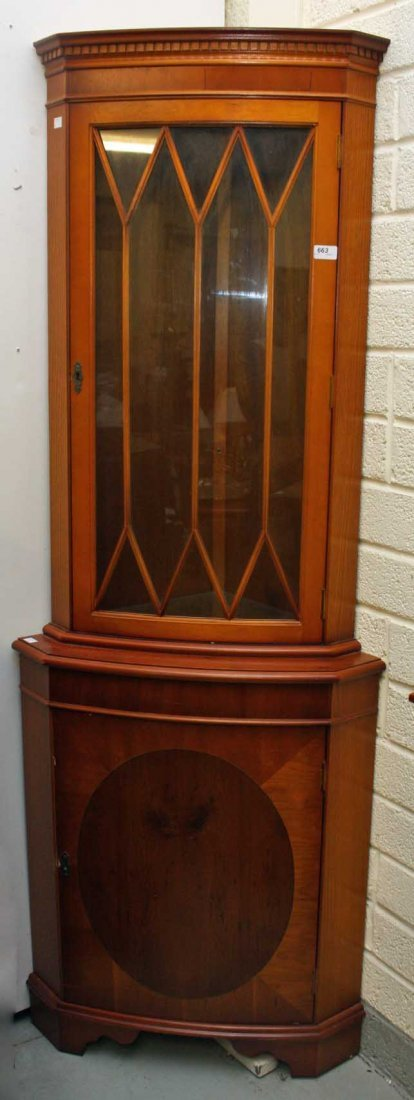 A SATIN COLOURED YEW AND BEECH CORNER CUPBOARD,  O.R.M,
